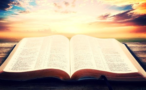 open bible with beautiful sky in background