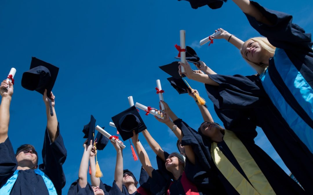 graduates holding caps and diplomas above their heads